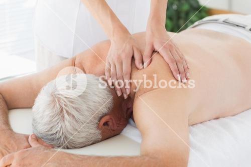 Therapist massaging back of senior man