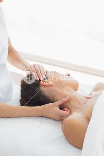 Relaxed woman receiving neck massage