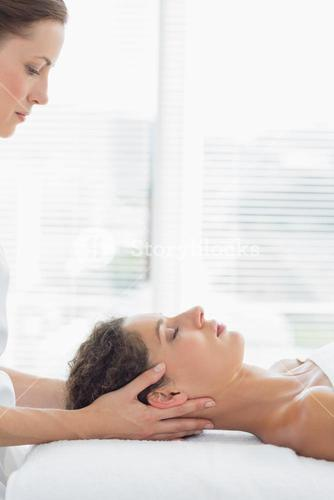Therapist massaging woman in health spa