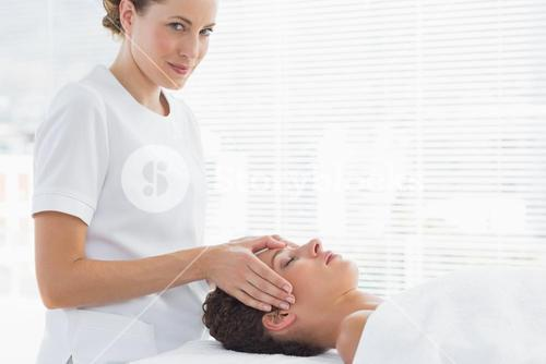 Therapist giving head massage to woman