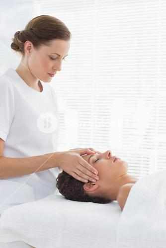 Female therapist giving head massage to woman