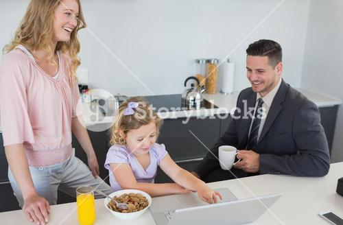 Parents with daughter using laptop during breakfast time