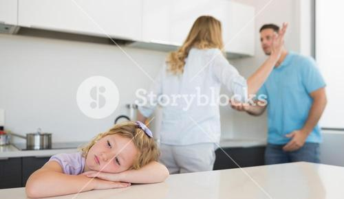 Bored girl leaning on table while parents arguing