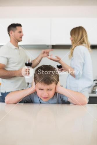 Irritated boy covering ears while parents arguing