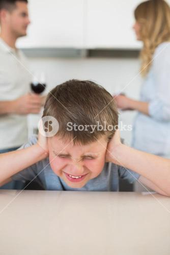 Furstrated boy covering ears while parents arguing