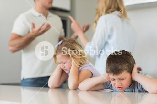 Children covering ears while parents arguing