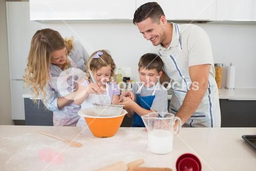 Family preparing cookies at kitchen counter
