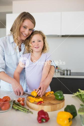 Mother assisting daughter in chopping capsicum
