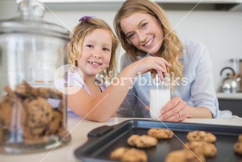 Mother with girl dipping cookie in milk