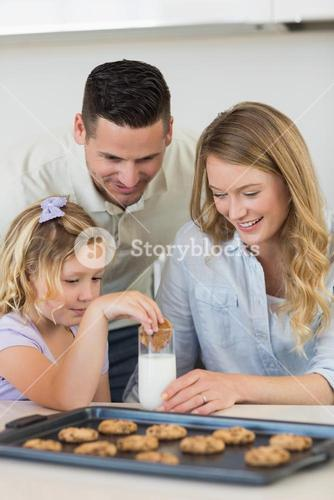 Parents looking at daughter dipping cookie in milk