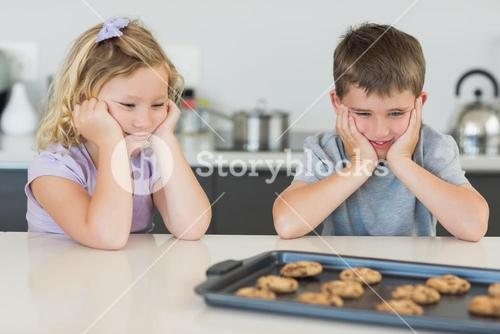 Brother and sister looking at tempting cookies