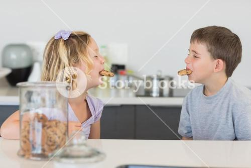 Siblings with cookies in mouth at kitchen counter