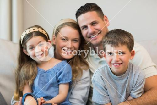 Parents and children sitting on sofa