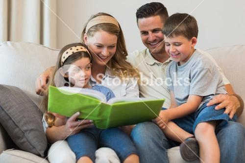 Family watching photo album on sofa