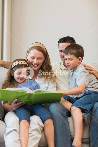 Family watching photo album on sofa at home