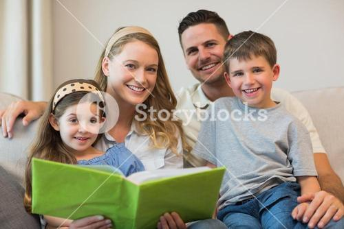 Family with photo album sitting on sofa