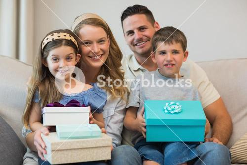 Happy family with gifts on sofa