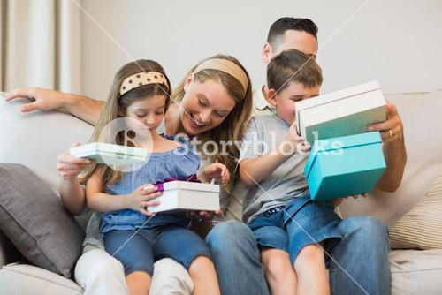 Family opening gifts on sofa