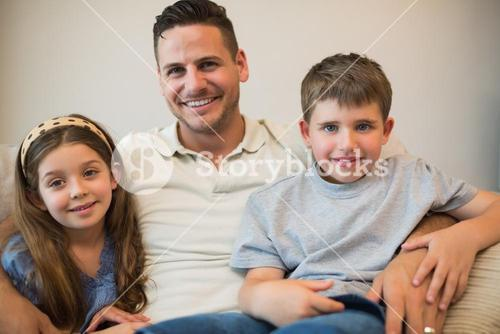 Father and children smiling on sofa