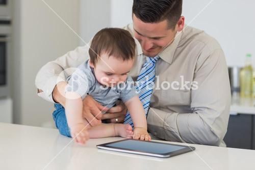 Businessman holding baby using tablet computer