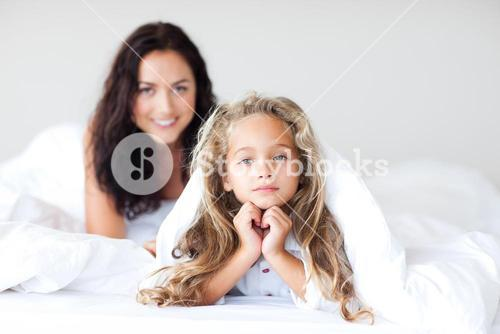 Young Mother and daugther having fun on bed