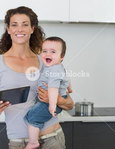 Mother with tablet computer carrying cheerful baby