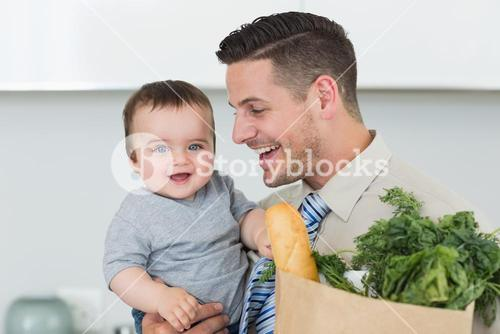 Happy baby being carried by businessman