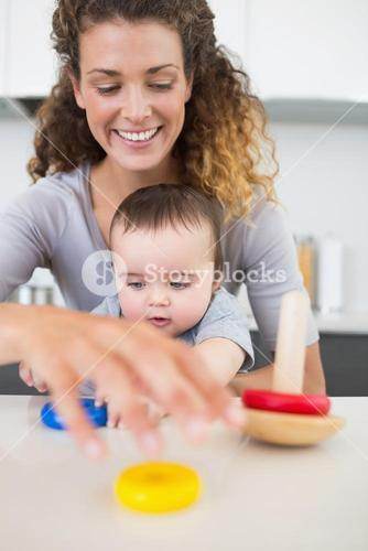 Mother and baby playing with toys at counter