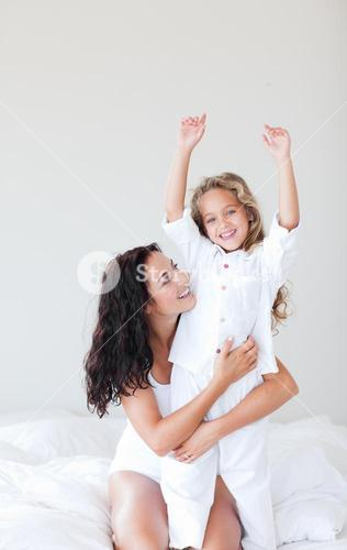 Happy mother and daugther embracing on bed