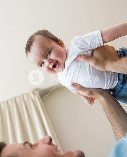 cheerful baby being carried by father