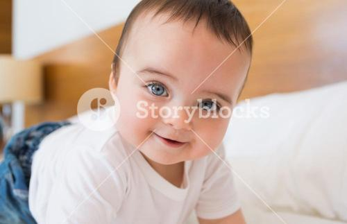 Smiling baby boy in bed