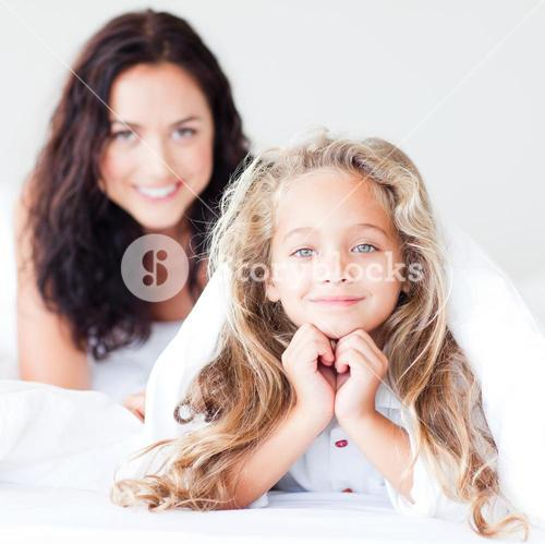 Charming mother and daugther embracing on bed