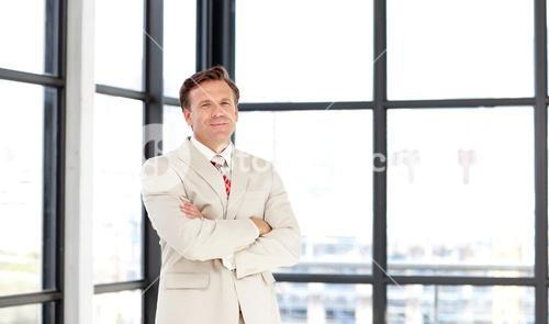 Business manager with folded arms looking at the camera