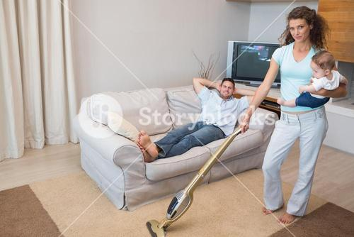 Woman cleaning house while carrying baby