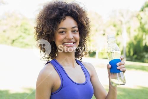 Confident sporty woman holding water bottle