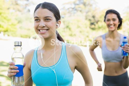 Fit women with water bottle jogging