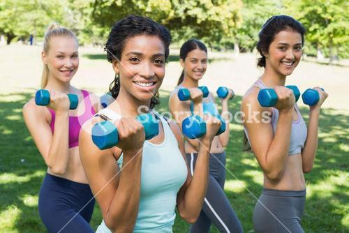 Confident sporty women lifting hands weights