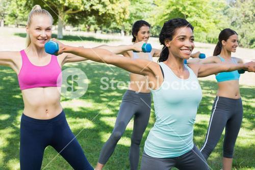 Sporty women lifting hands weights
