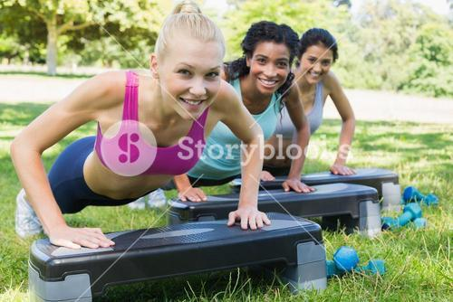 Sporty women doing step aerobics