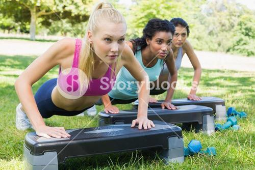 Determined women doing step aerobics
