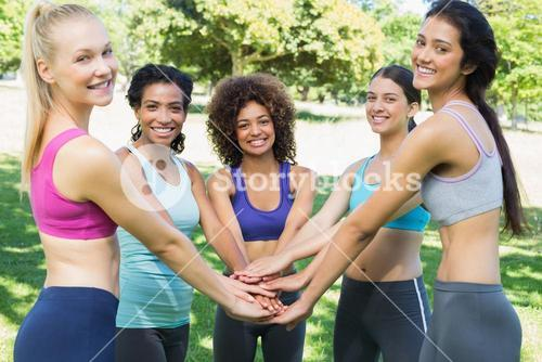 Female friends stacking hands in park