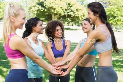 Female friends with hands stacked together