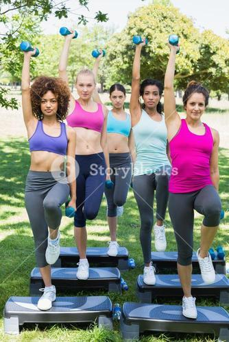 Determined women doing step aerobics in park