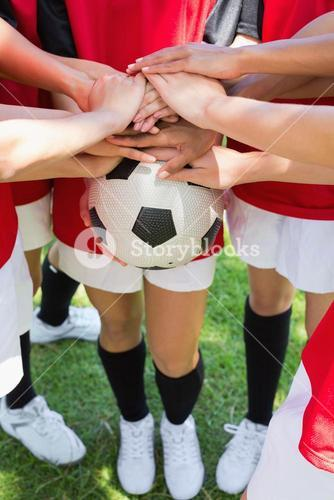 Soccer team stacking hands on ball