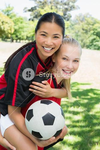 Female soccer player piggybacking teammate