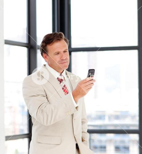 Portrait of a businessman sending a text on a mobilephone