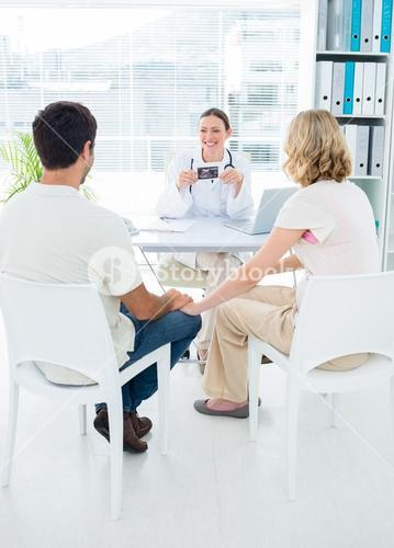 Expectant couple consulting gynaecologist