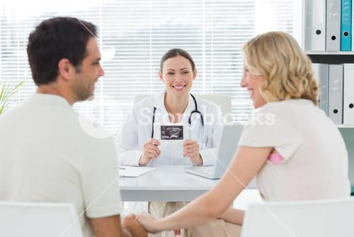Gynaecologist looking at expectant couple