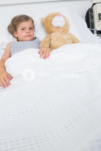 Girl with teddy bear lying in hospital bed