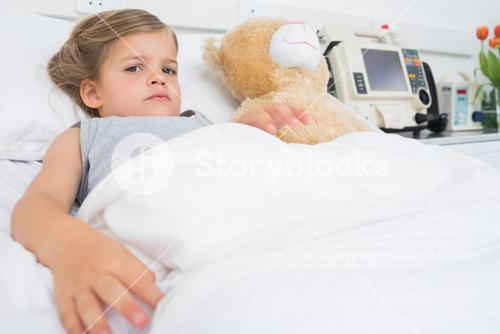 Cute girl lying in hospital bed